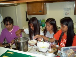 Mawli and friends Rem Chin, Bawimen, and Universal cook traditional a traditional Burmese dish for their classmates.